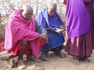 Elders praying over a bible passage